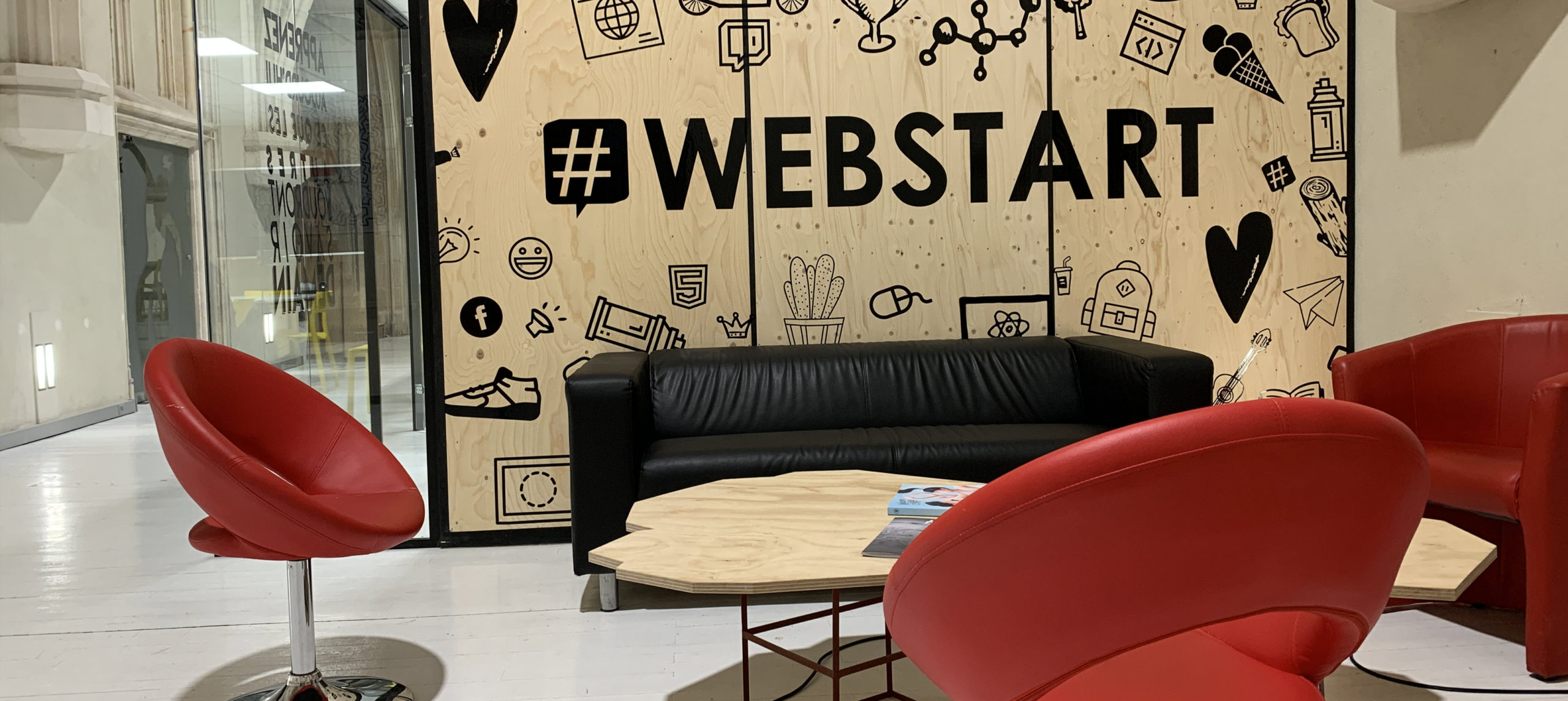 Un panneau Webstart en noir sur fond bois et un canapé