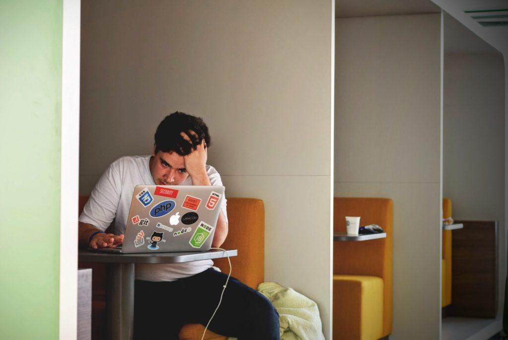 garçon qui travaille derrière un ordinateur mac book pro